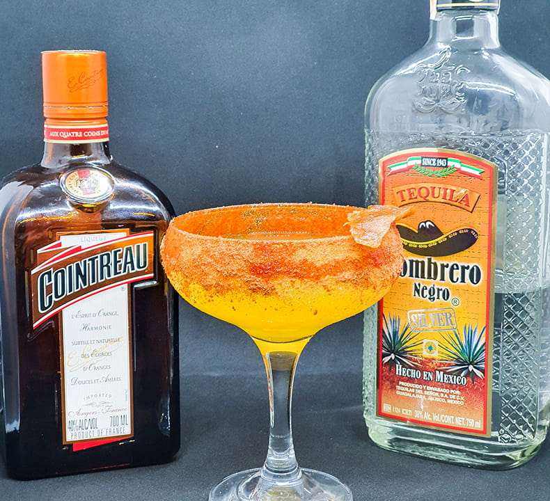 Bottle of Cointreau and Sombrero Negro Tequila and a glass of cocktail drink