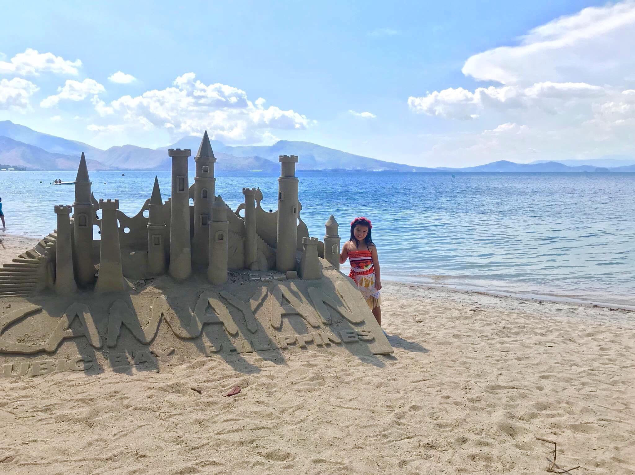 Girl standing next to sand castle